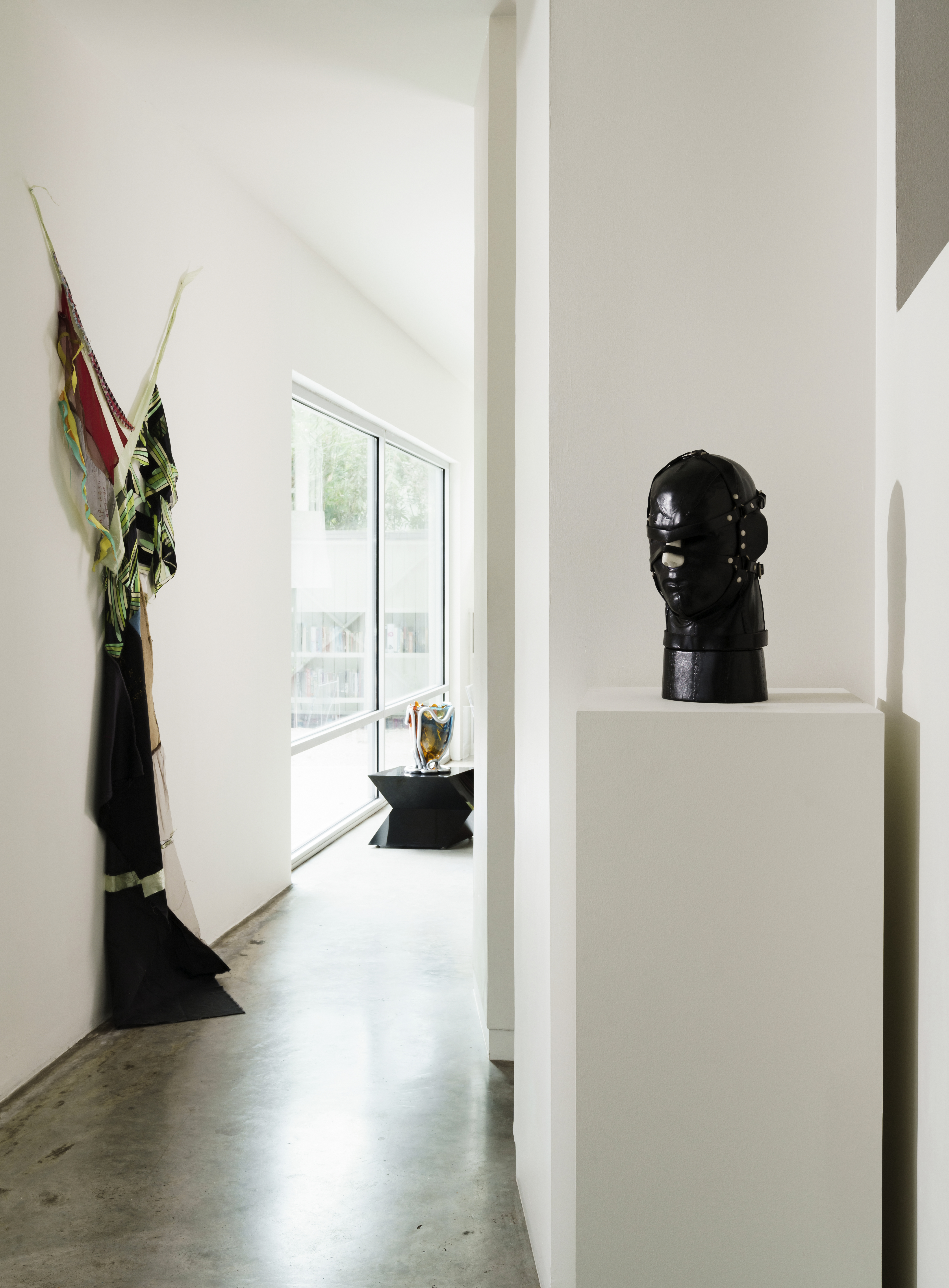 In the hall is a work by Eric N. Mack and to the right is an iconic leather heads by Nancy Grossman.