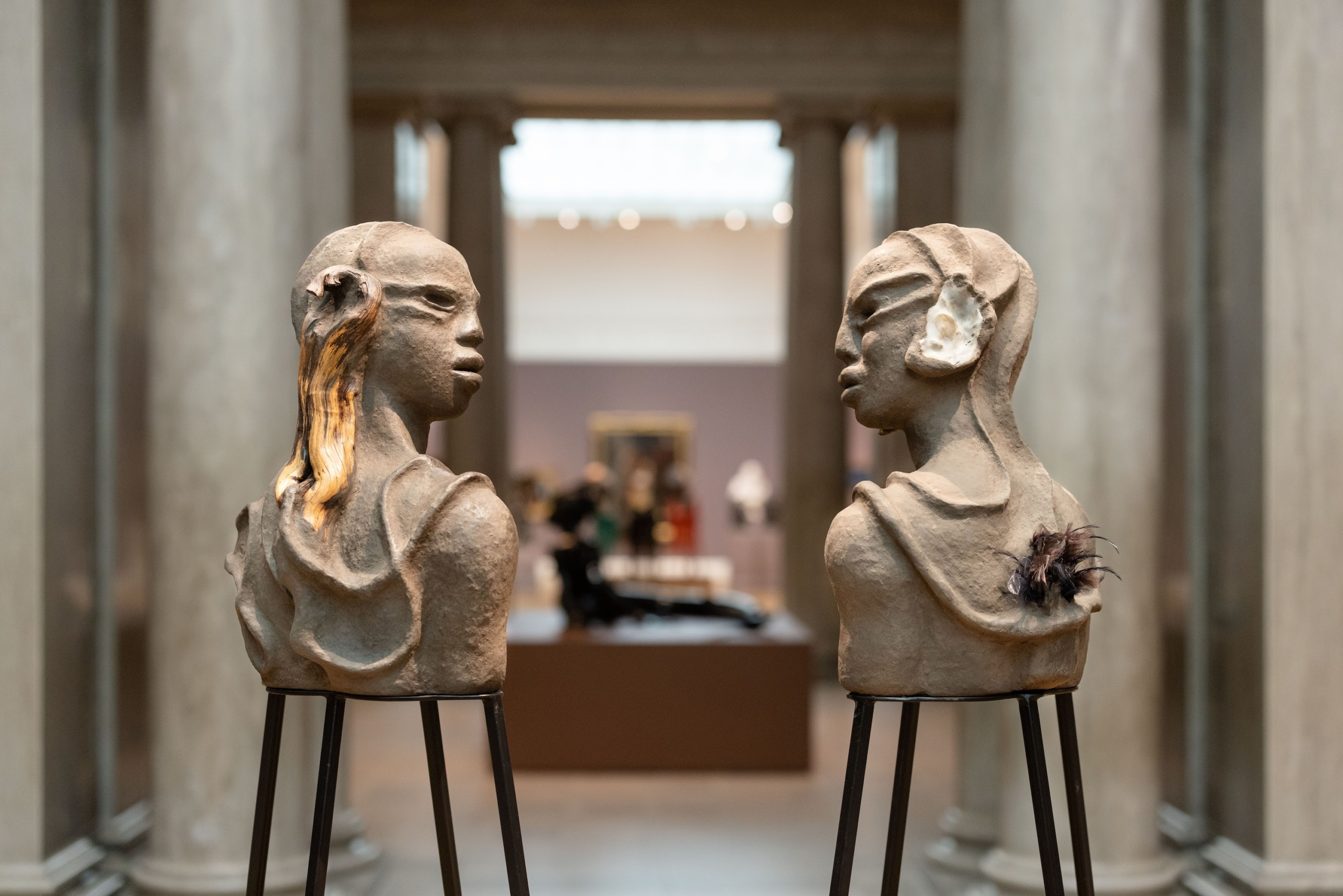 Two bust sculptures facing each other in museum space