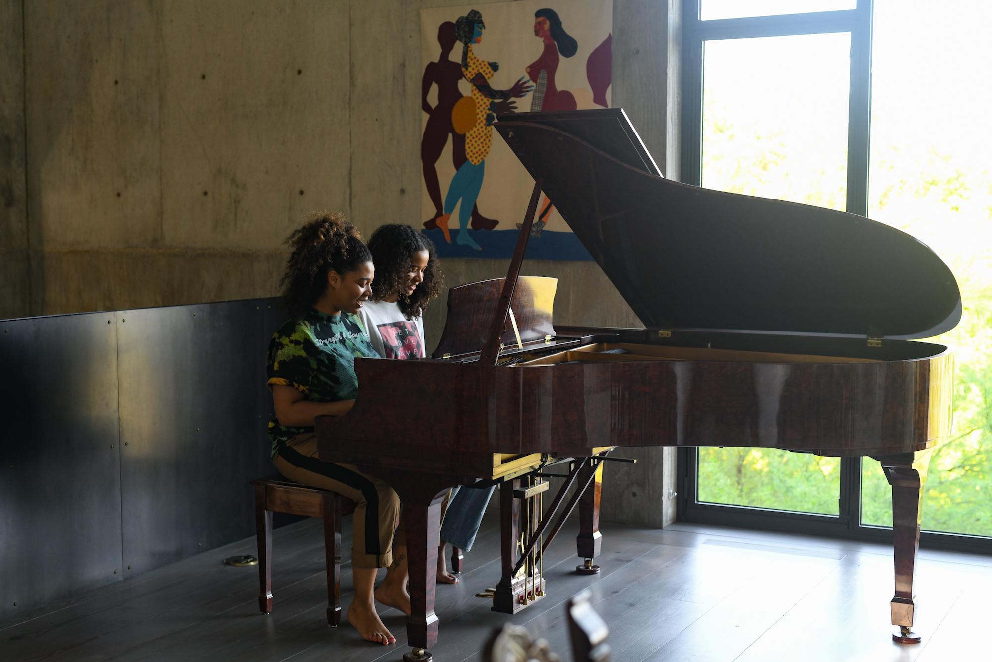 Two girls playing piano