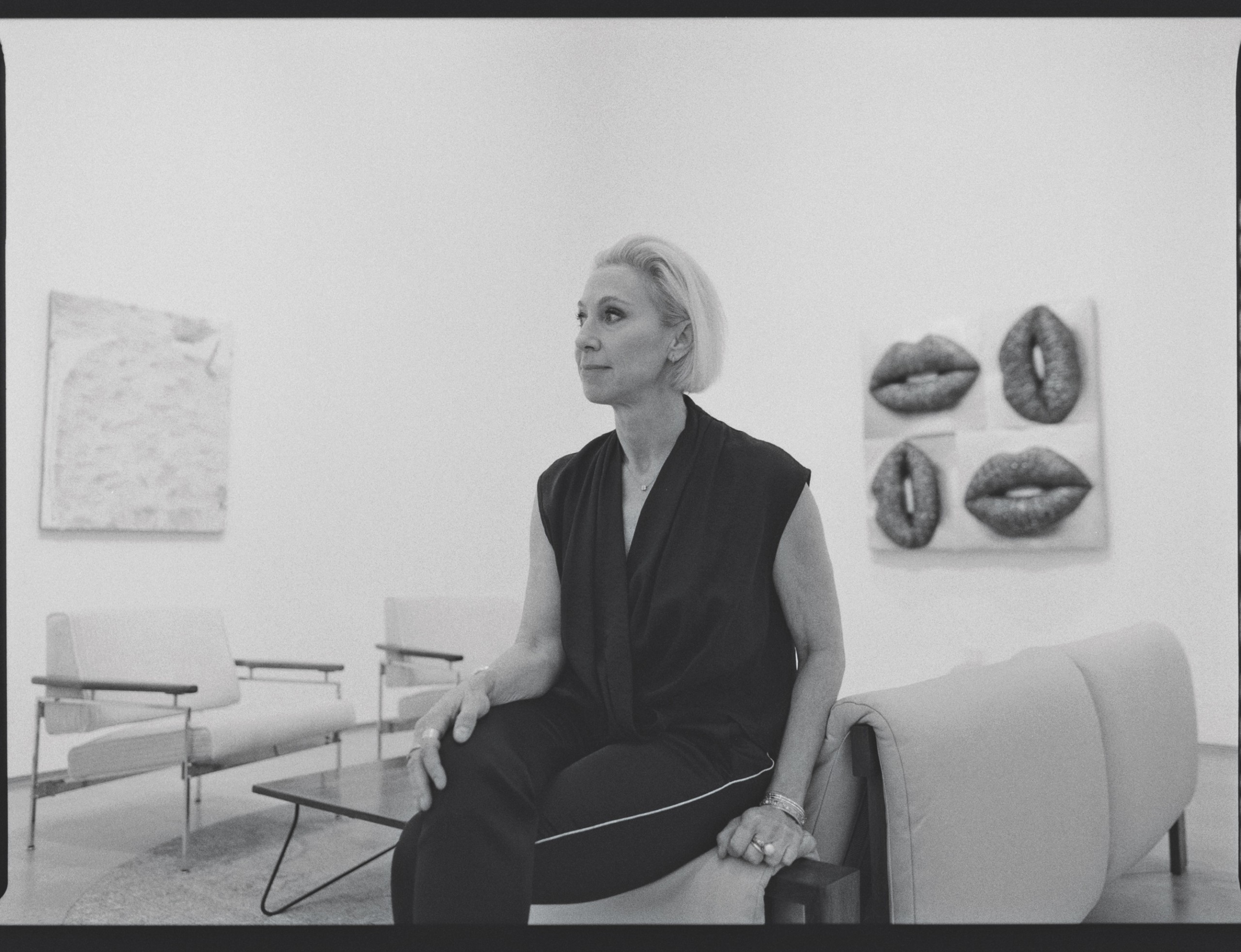 Black and white image of art gallerist sitting in her office space, side profile