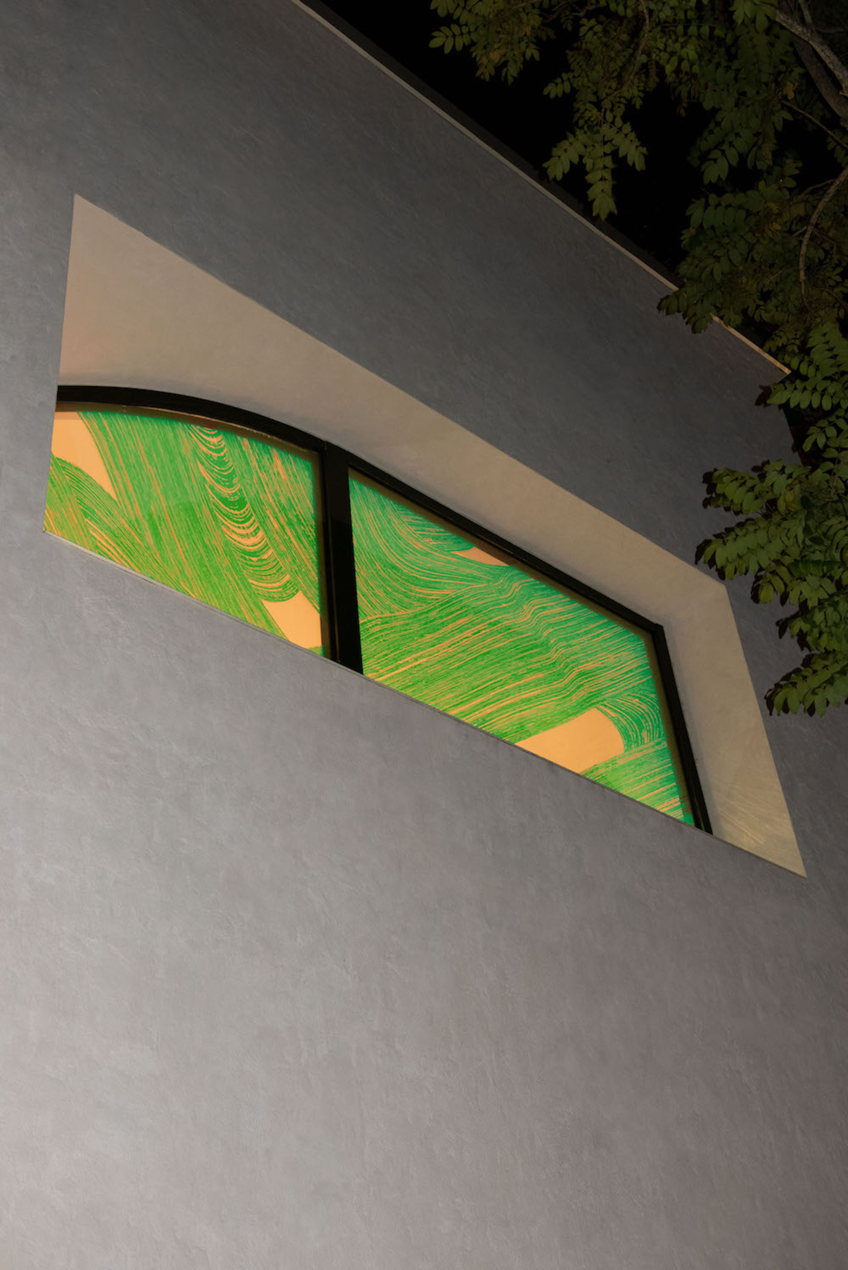 Dark storefront illuminated by window with knotlike pattern embossed on glass