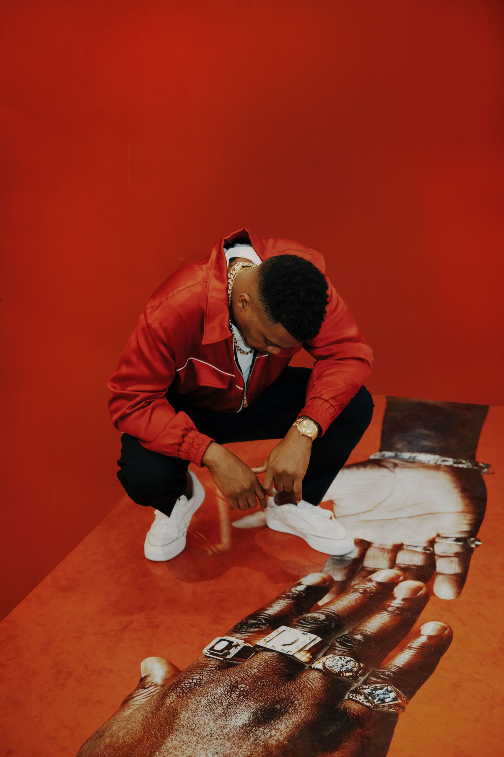 Man in red leather jacket against red wall squatting and looking at art of a hand on floor