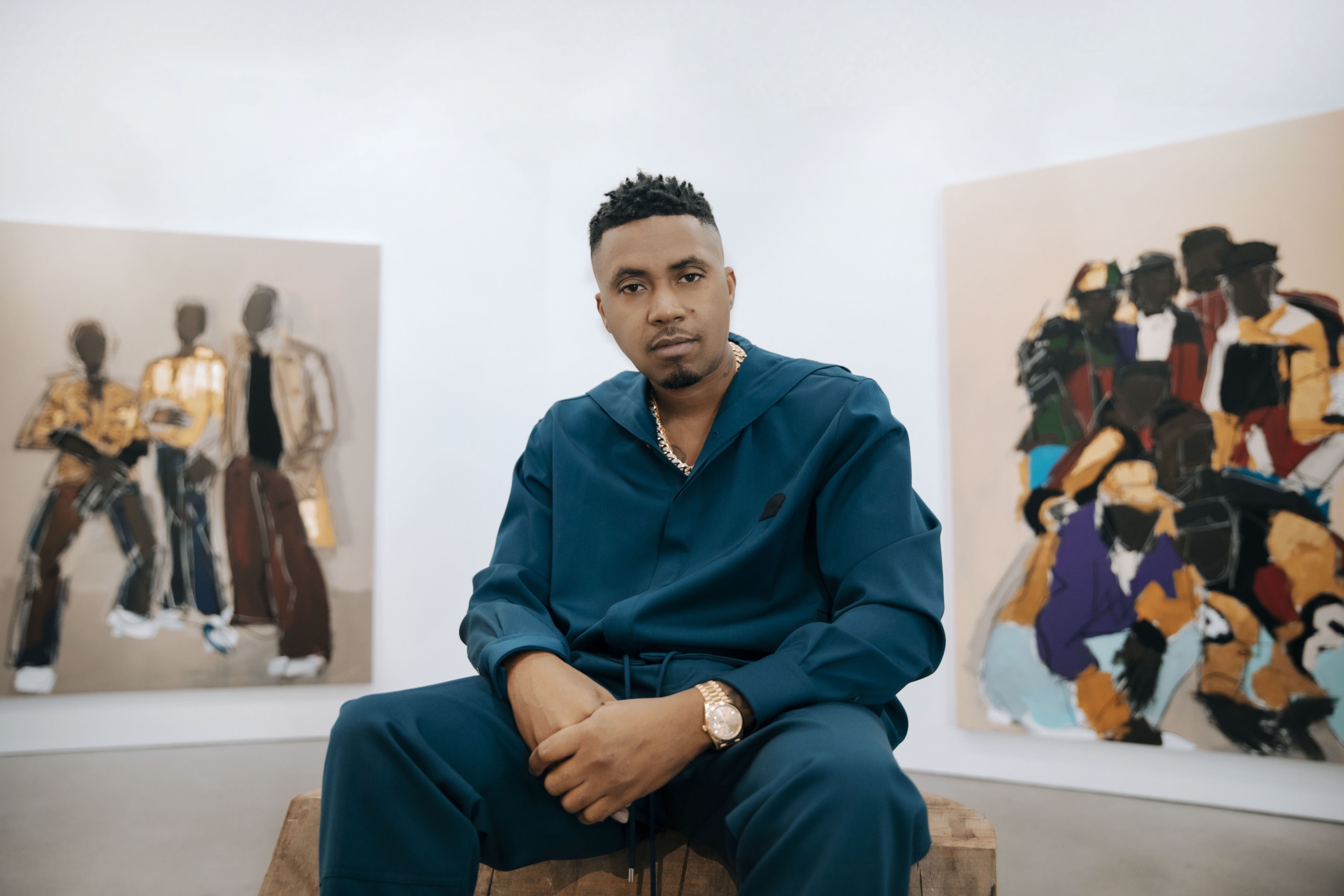 Musician sitting in gallery space, in front of 2 paintings