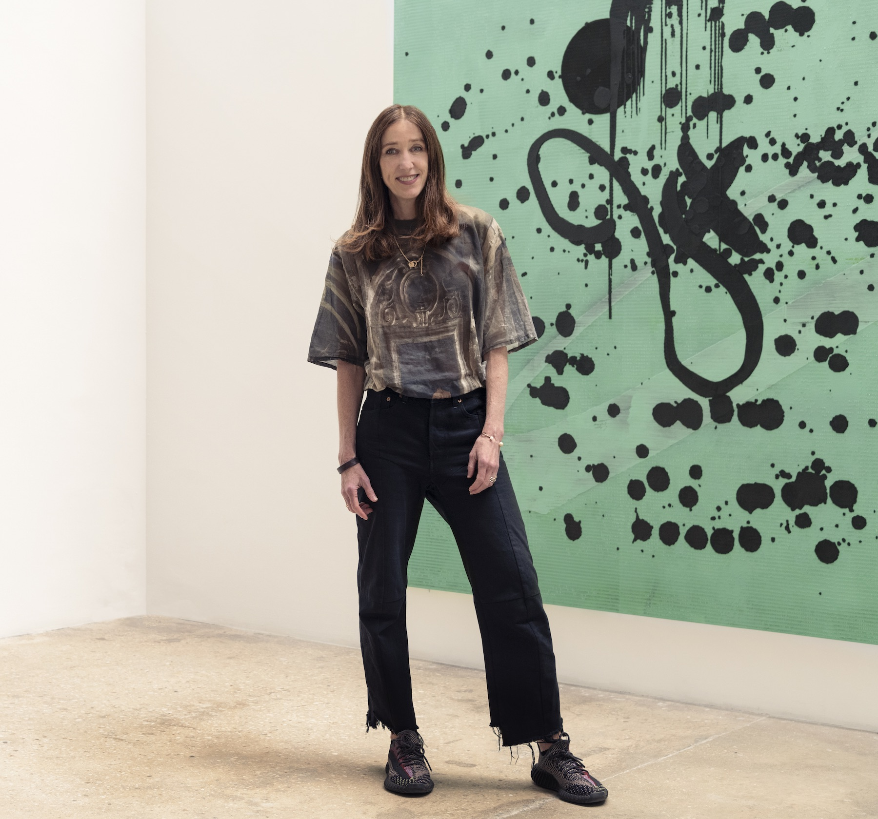 Female art gallerist standing in front of abstract painting