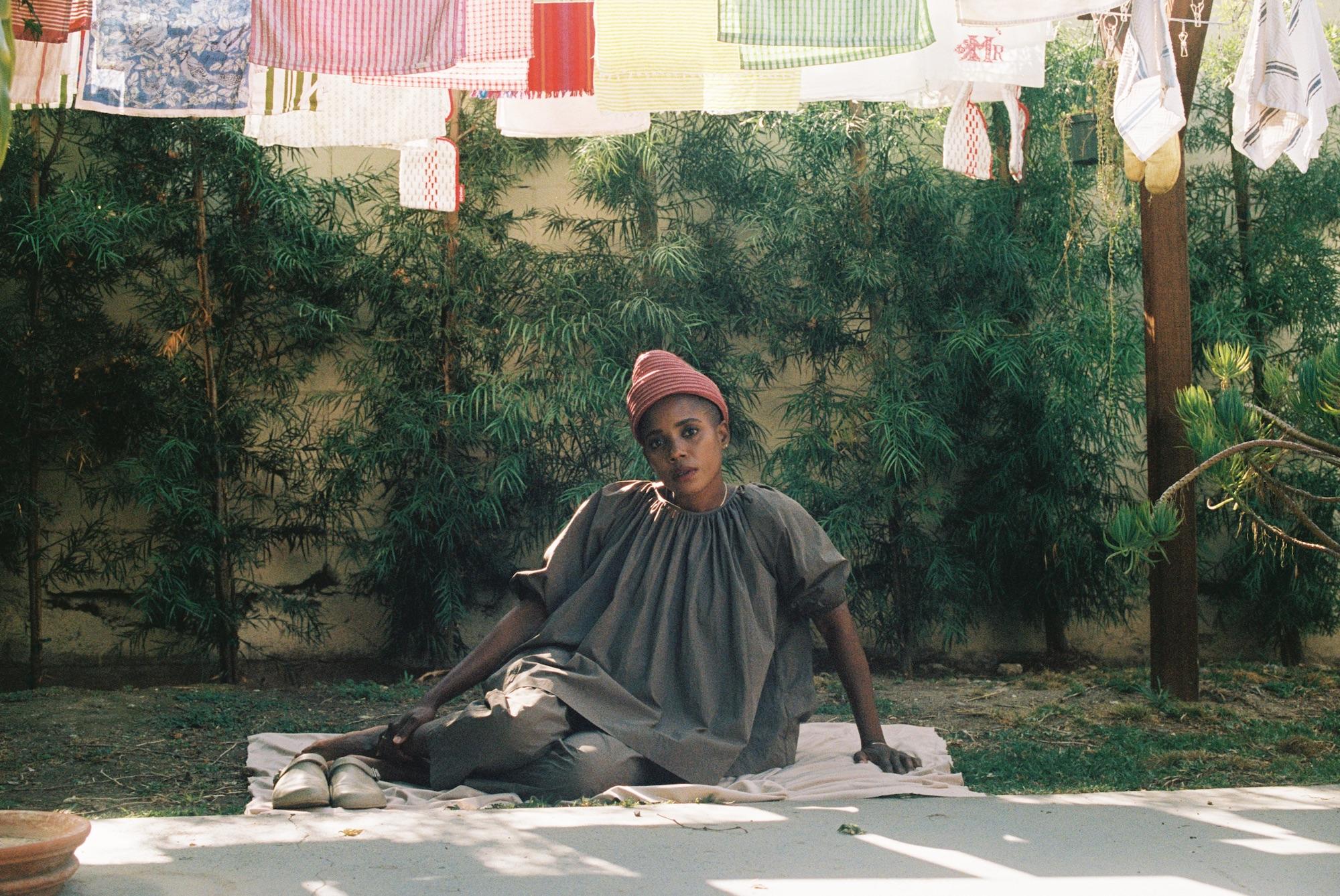 Woman sitting under clothesline