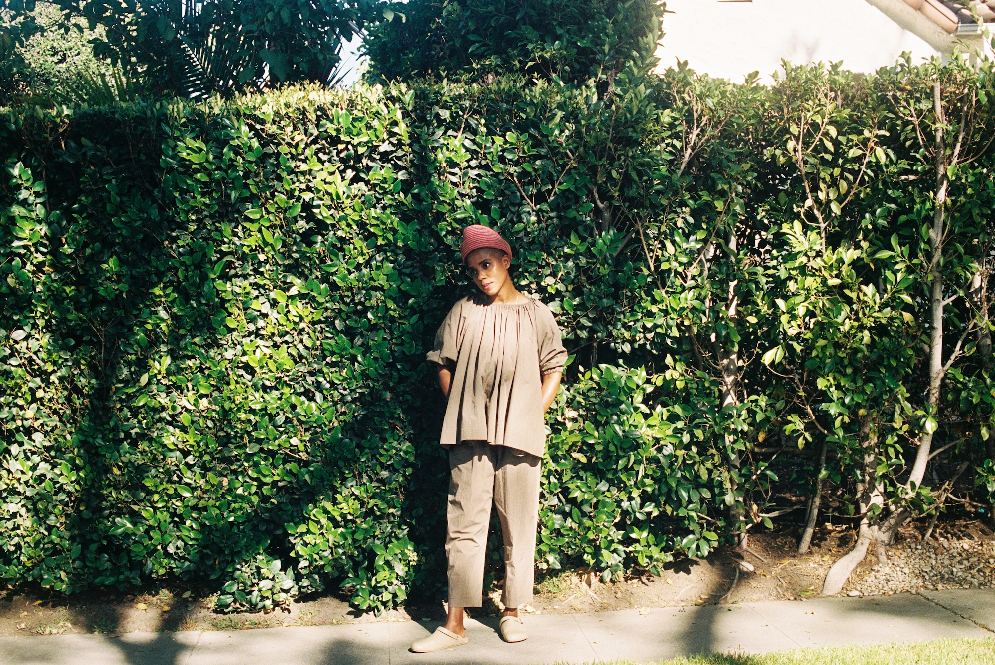 Woman standing in front of hedges janicza bravo