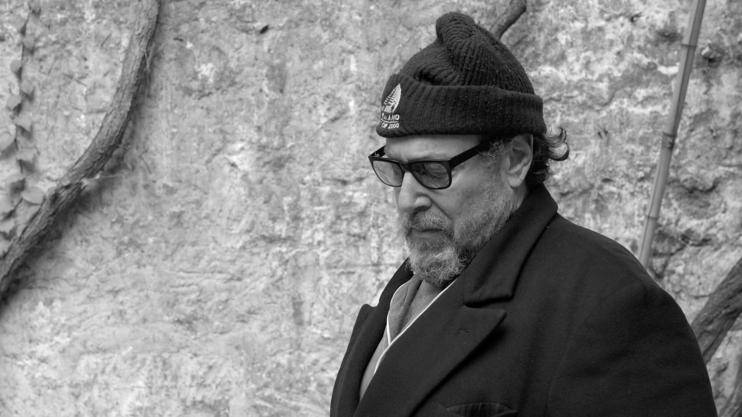 Black and white portrait of artist in beanie and glasses