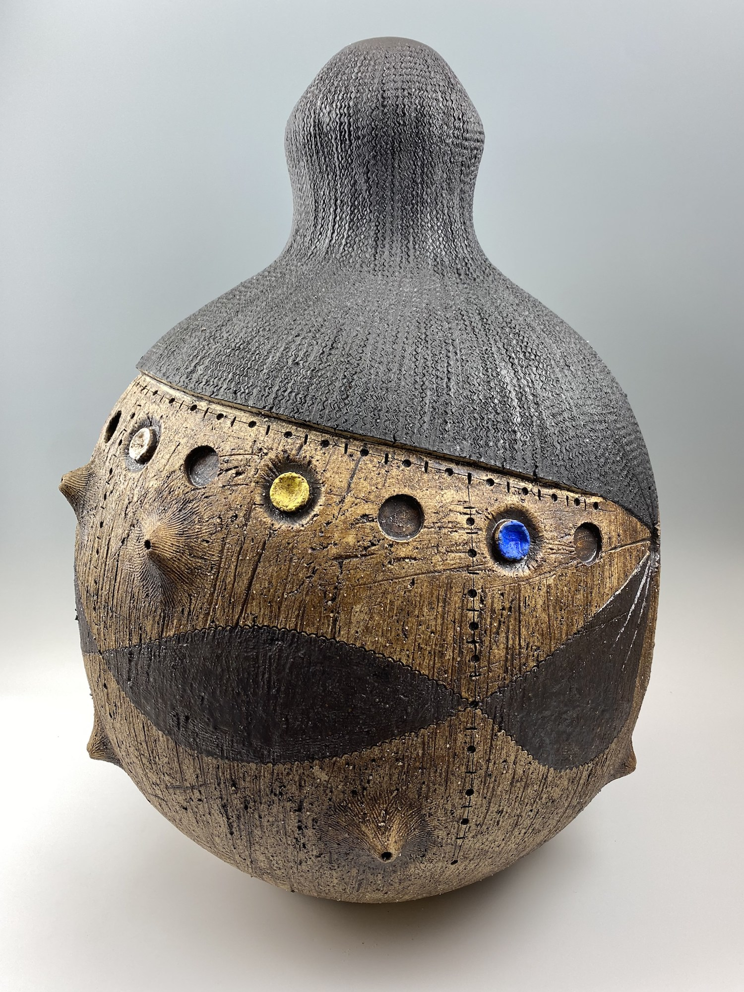 Pottery sculpture with African influences. Features colorful gems
