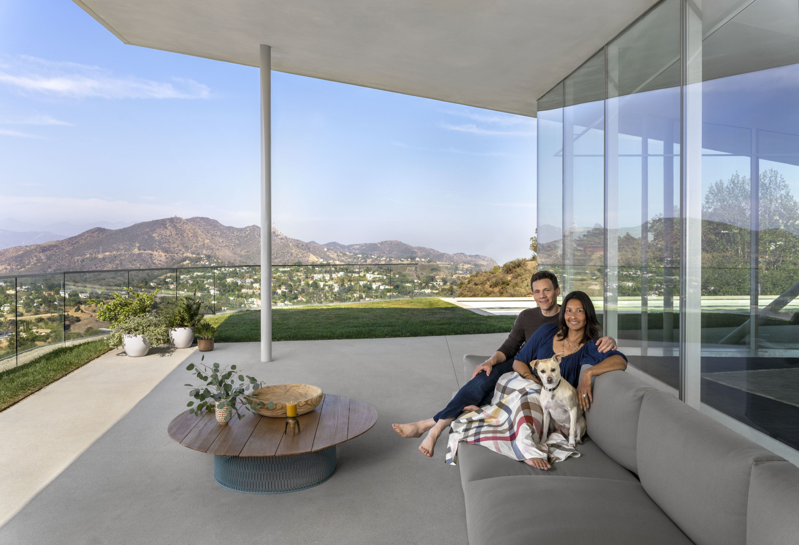 smiling couple sitting on outdoor couch on balcony of modern home, with mountains of LA in background