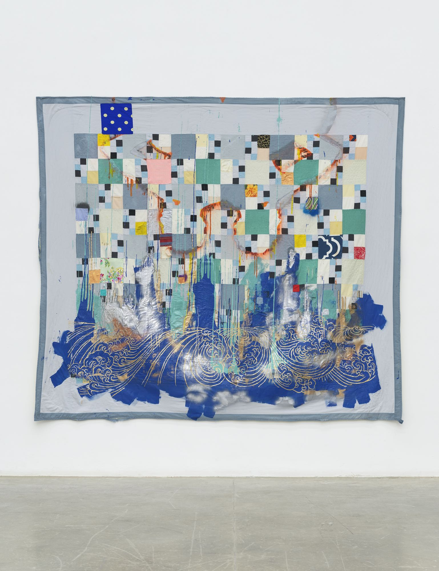 quilt by sanford biggers in gallery space, with square shapes in a pattern, and blue wave on the bottom