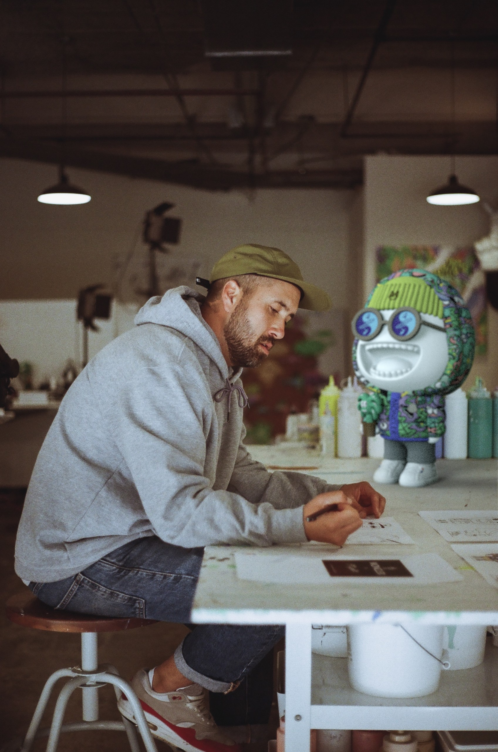 steven harrington sitting at work table with moncler pupazzo statue next to him