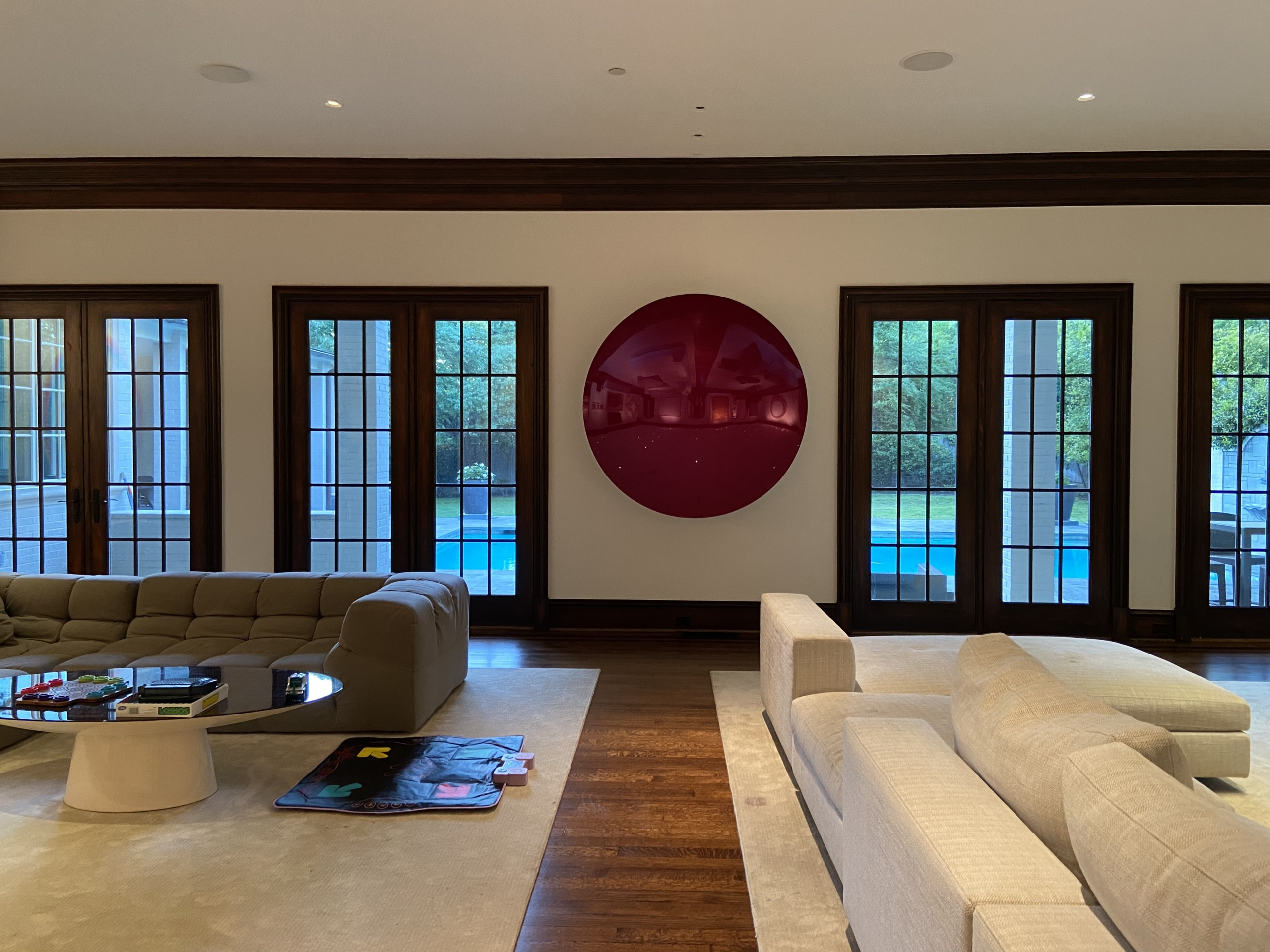 art collector's living room space with large couches and circular art piece hanging in between windows Mark Giambrone