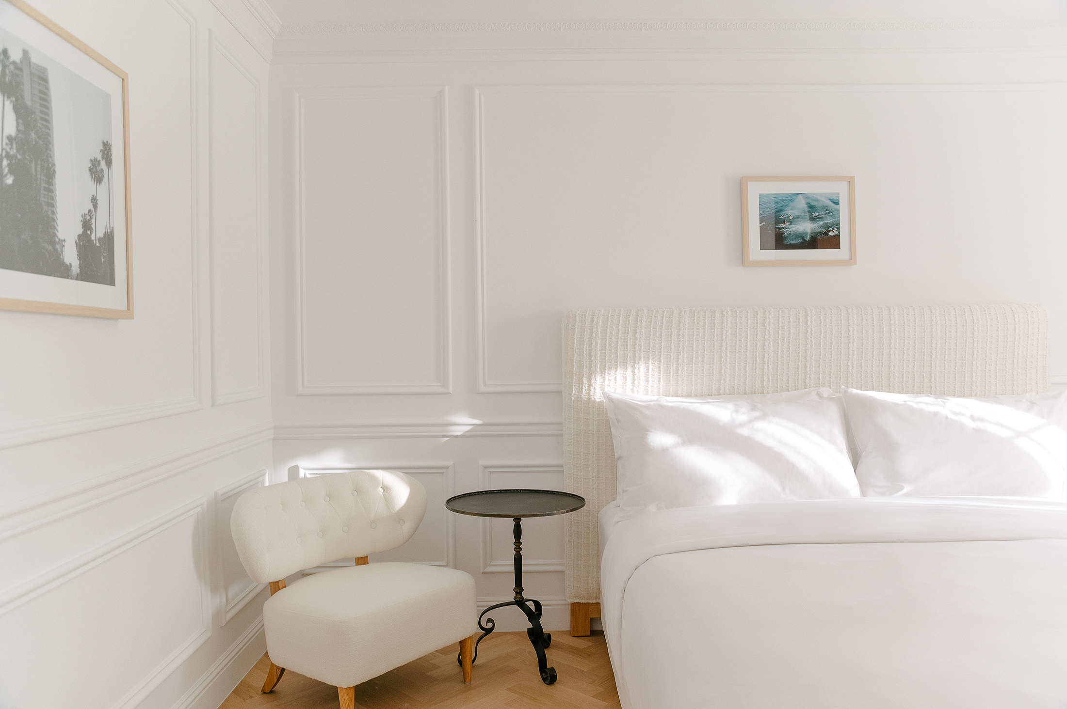 simple hotel bedroom with clean linens and simple chair