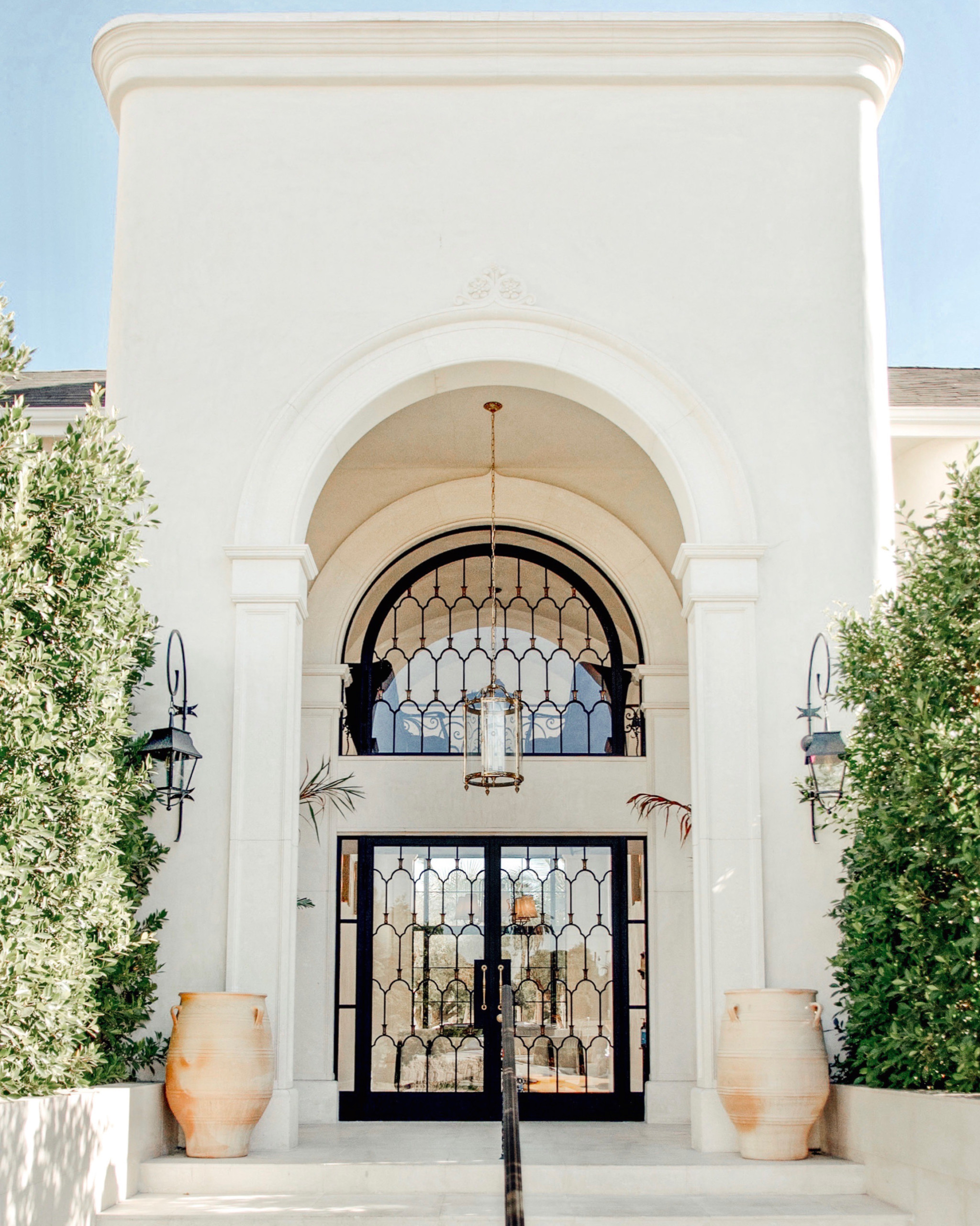 rustic hotel entrance flanked by tall trees and pottery, with large doors and mediterranean style chandelier