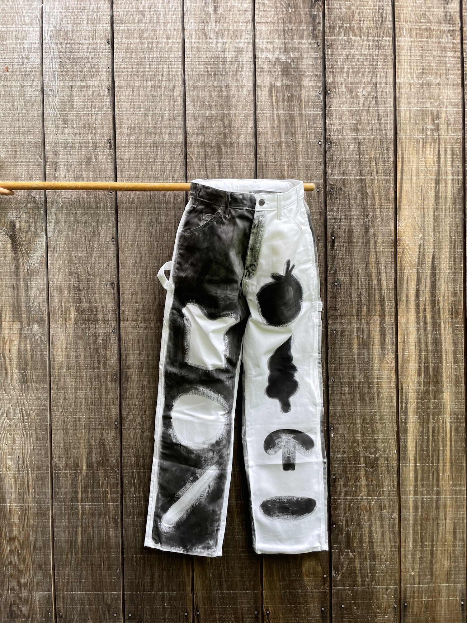 pants hanging on wooden pole against wood wall