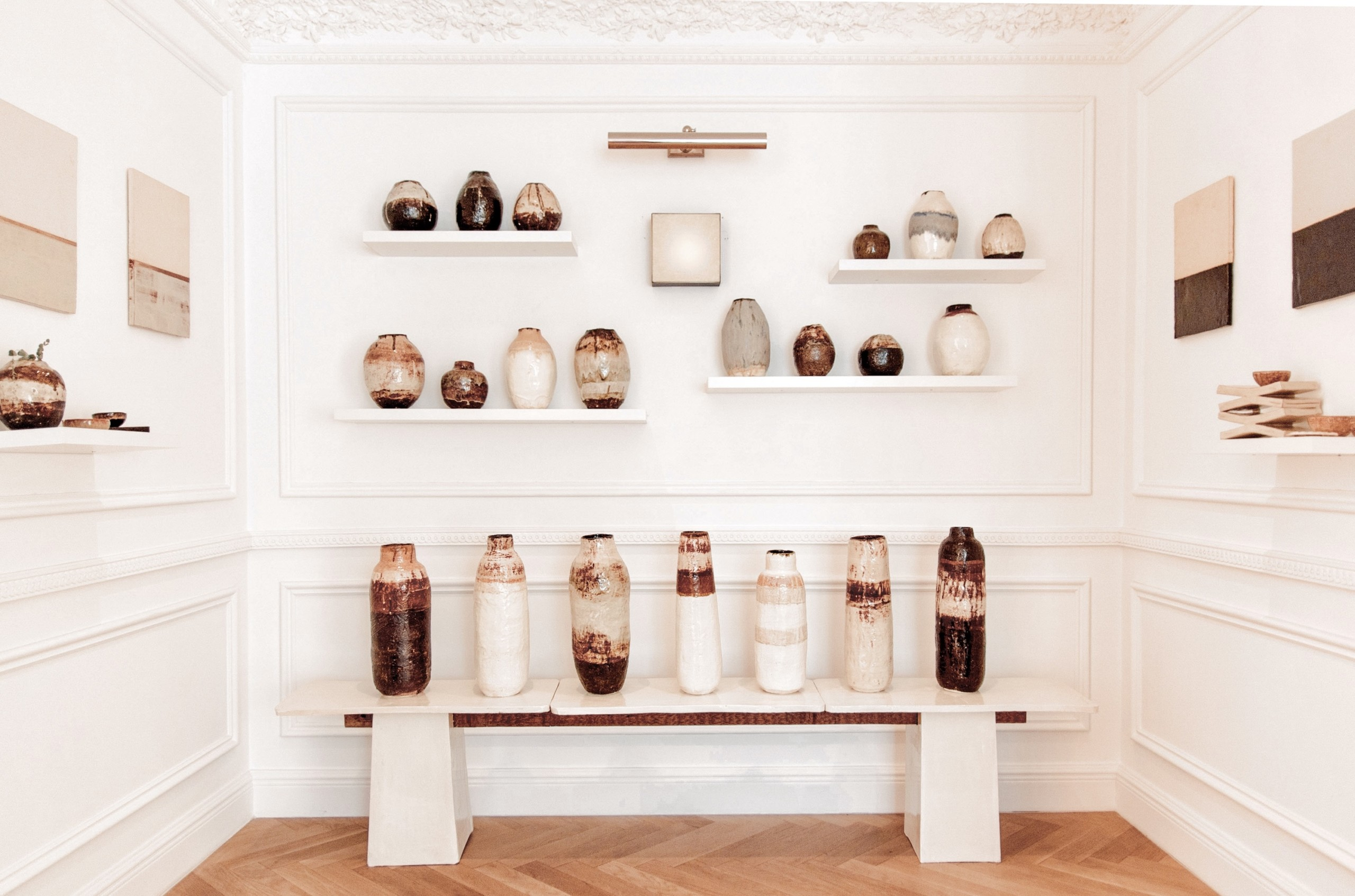 installation of earthy pottery, on benches and shelves in alcove