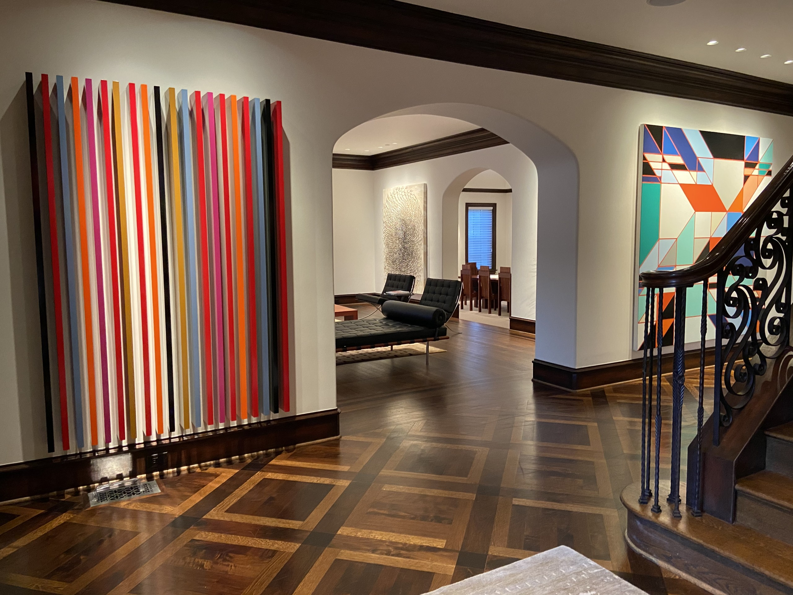 art collector's foyer with glimpse into living room space, with abstract artwork on walls Mark Giambrone