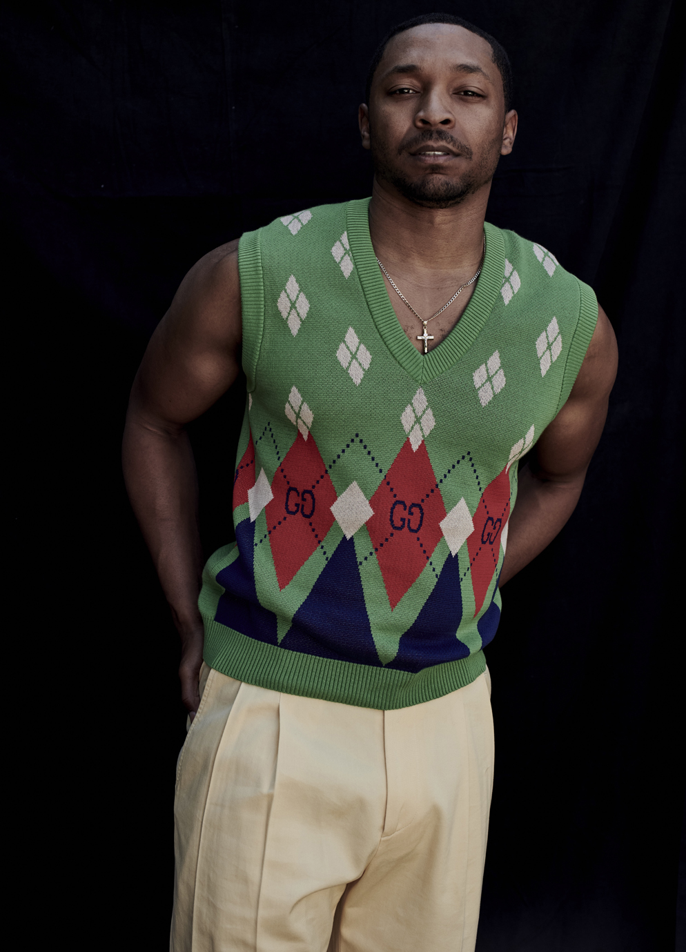 portrait of man in Gucci sweater vest against opaque background