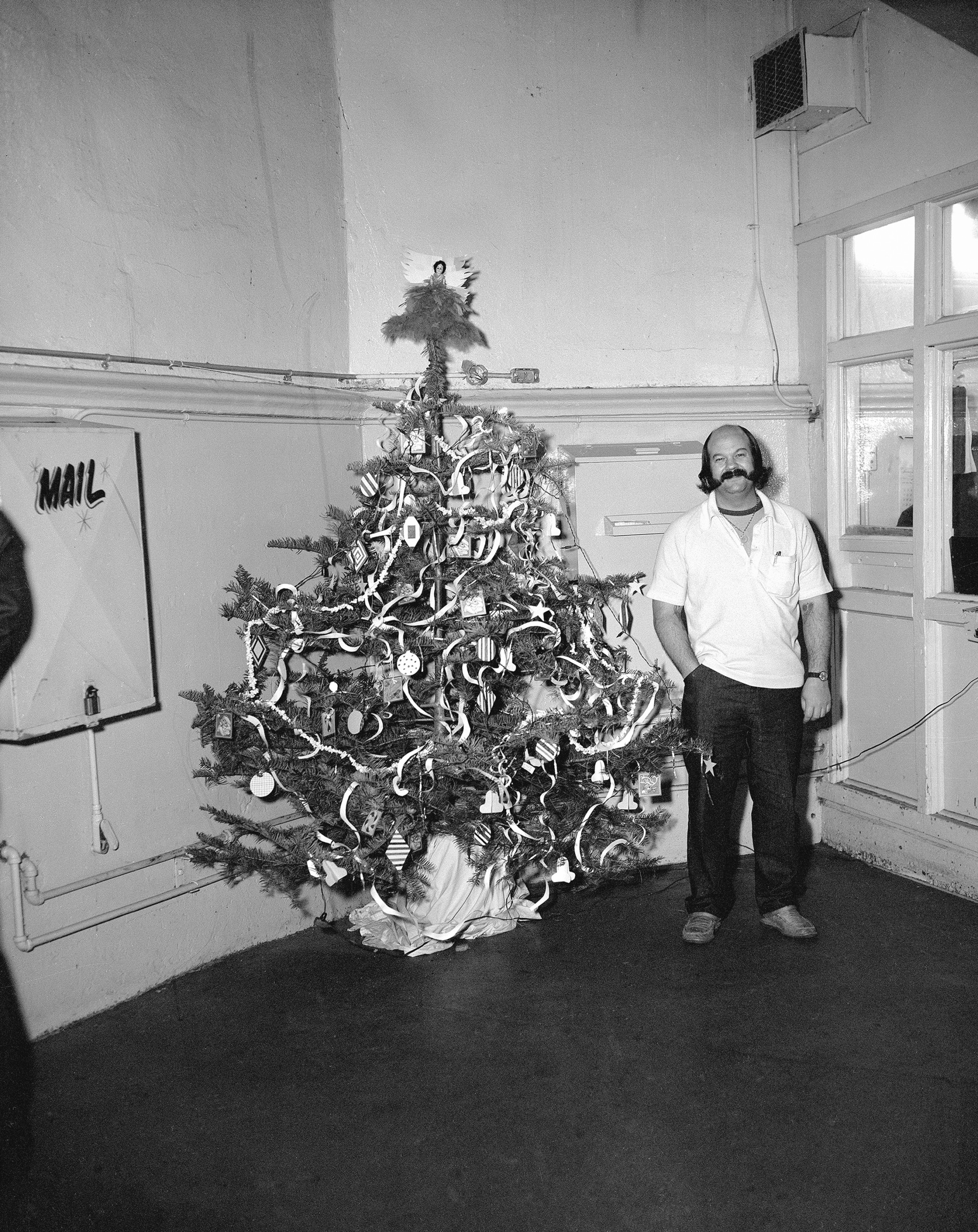 photograph of man in prison standing next to decorated christmas tree