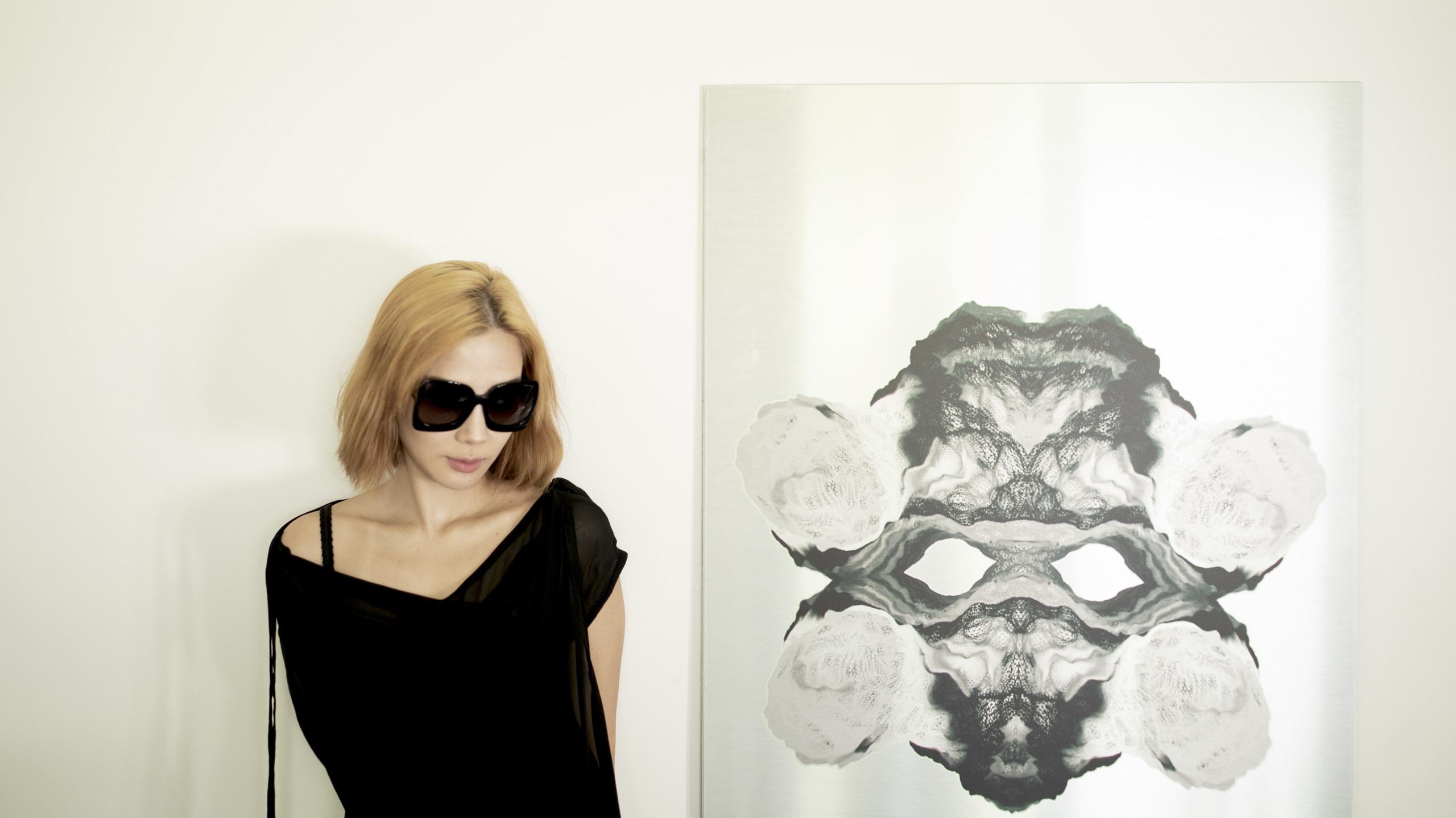 gallerist nalada taechanarong poses in sunglasses next to metal on canvas artwork