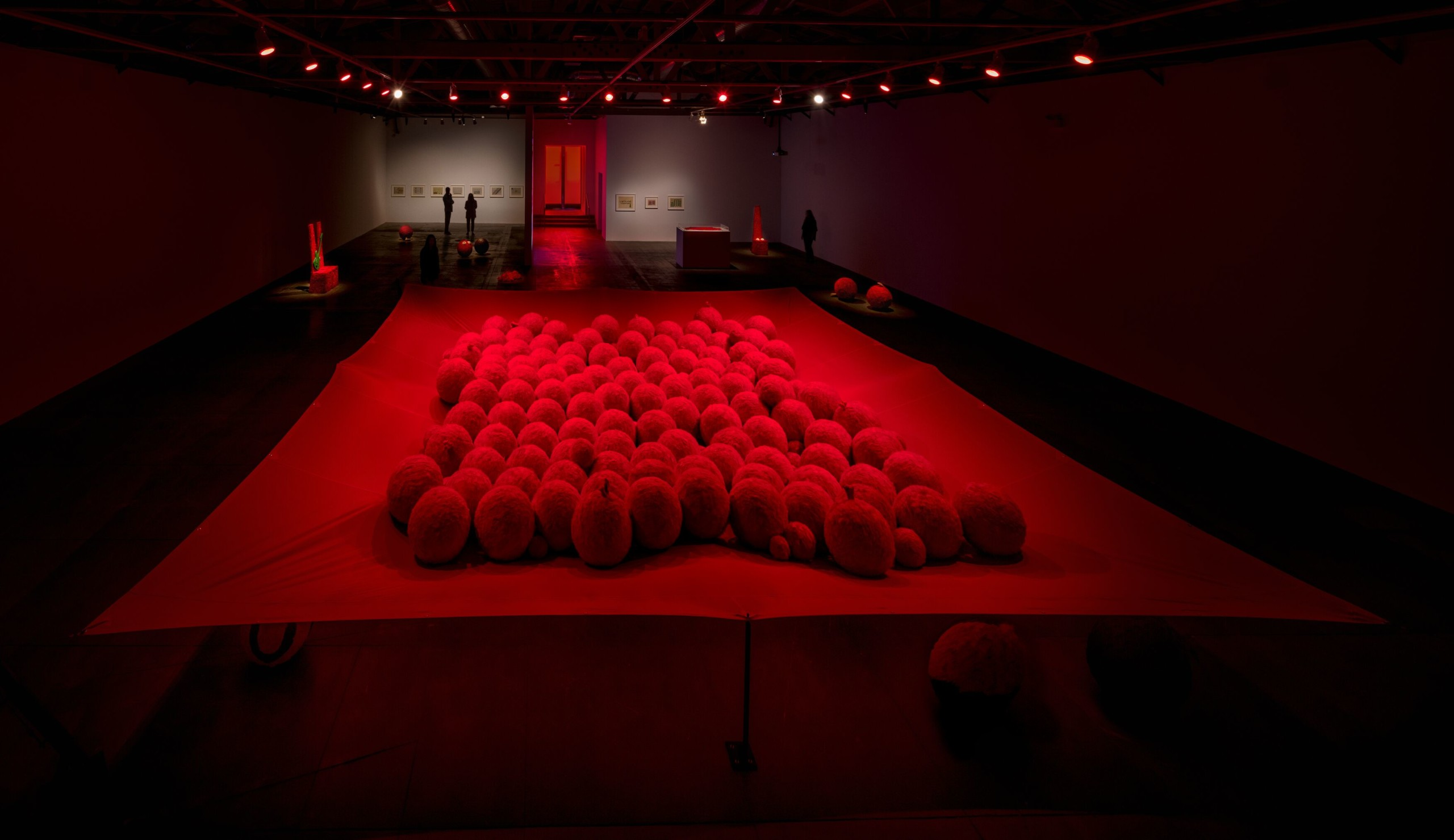 Gallery installation with red lighting on large-scale balls on fabric