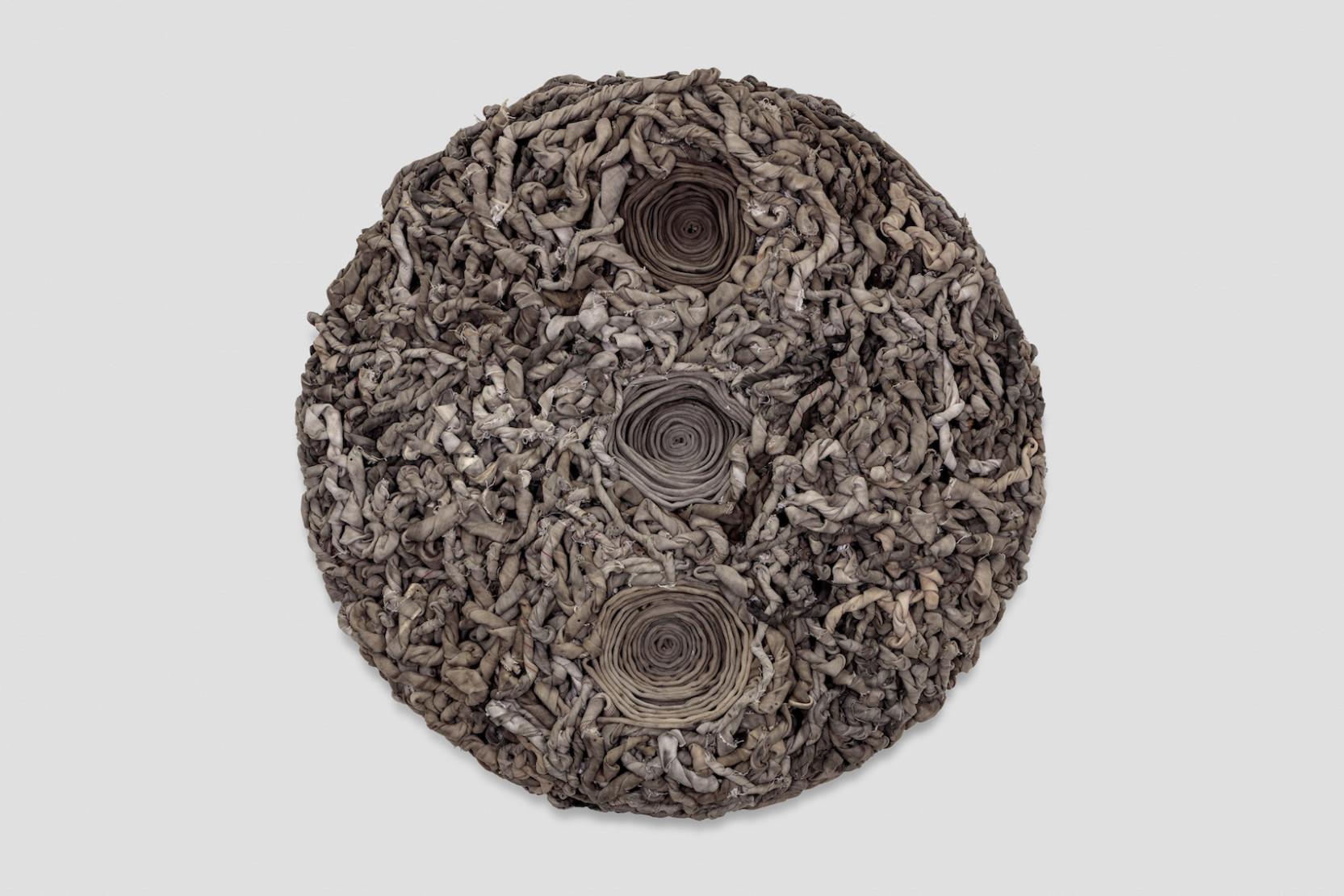 circular sculpture wall piece made of found materials by nari ward