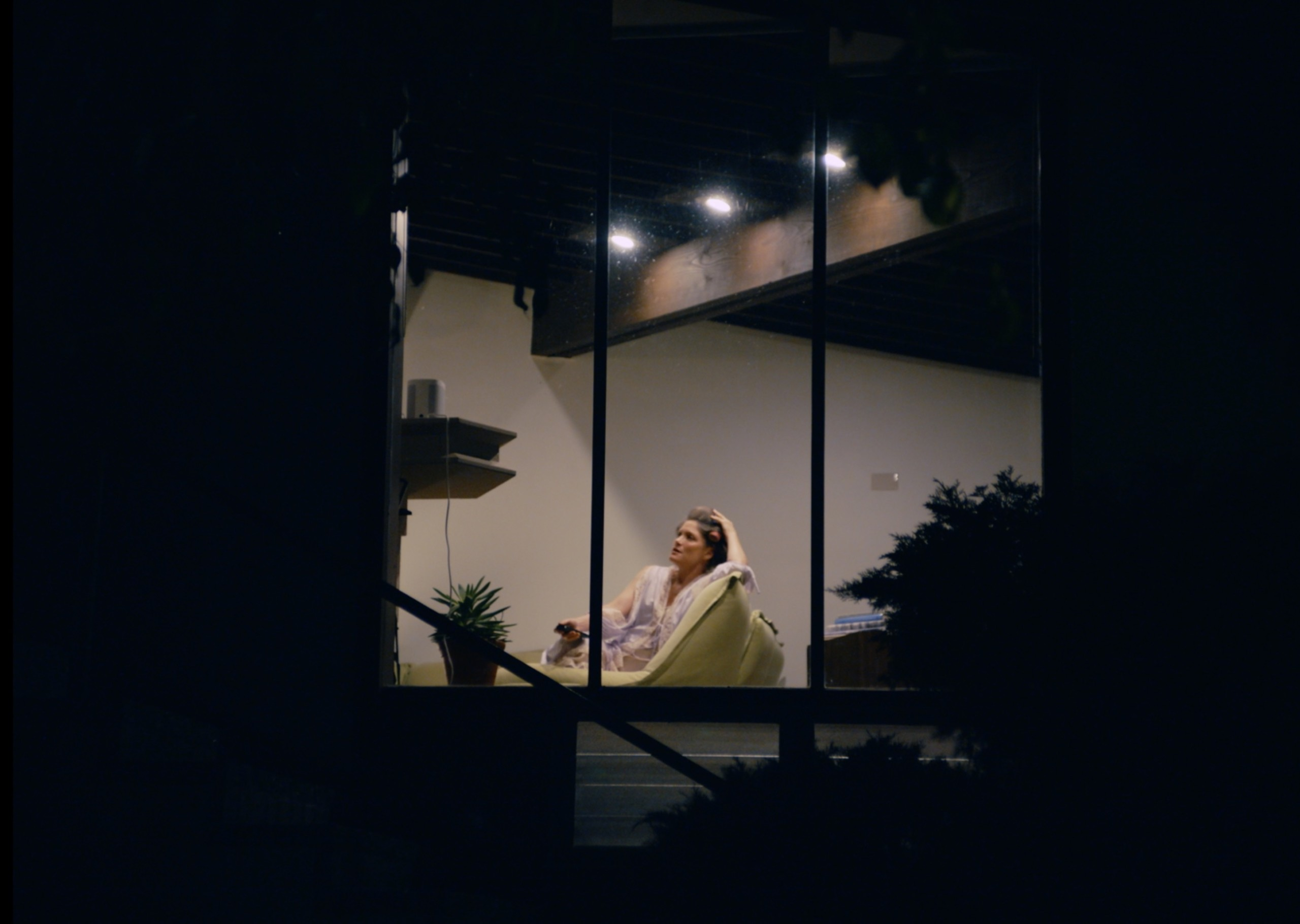 shot of woman from outside her home sitting on a chair with a drink at night