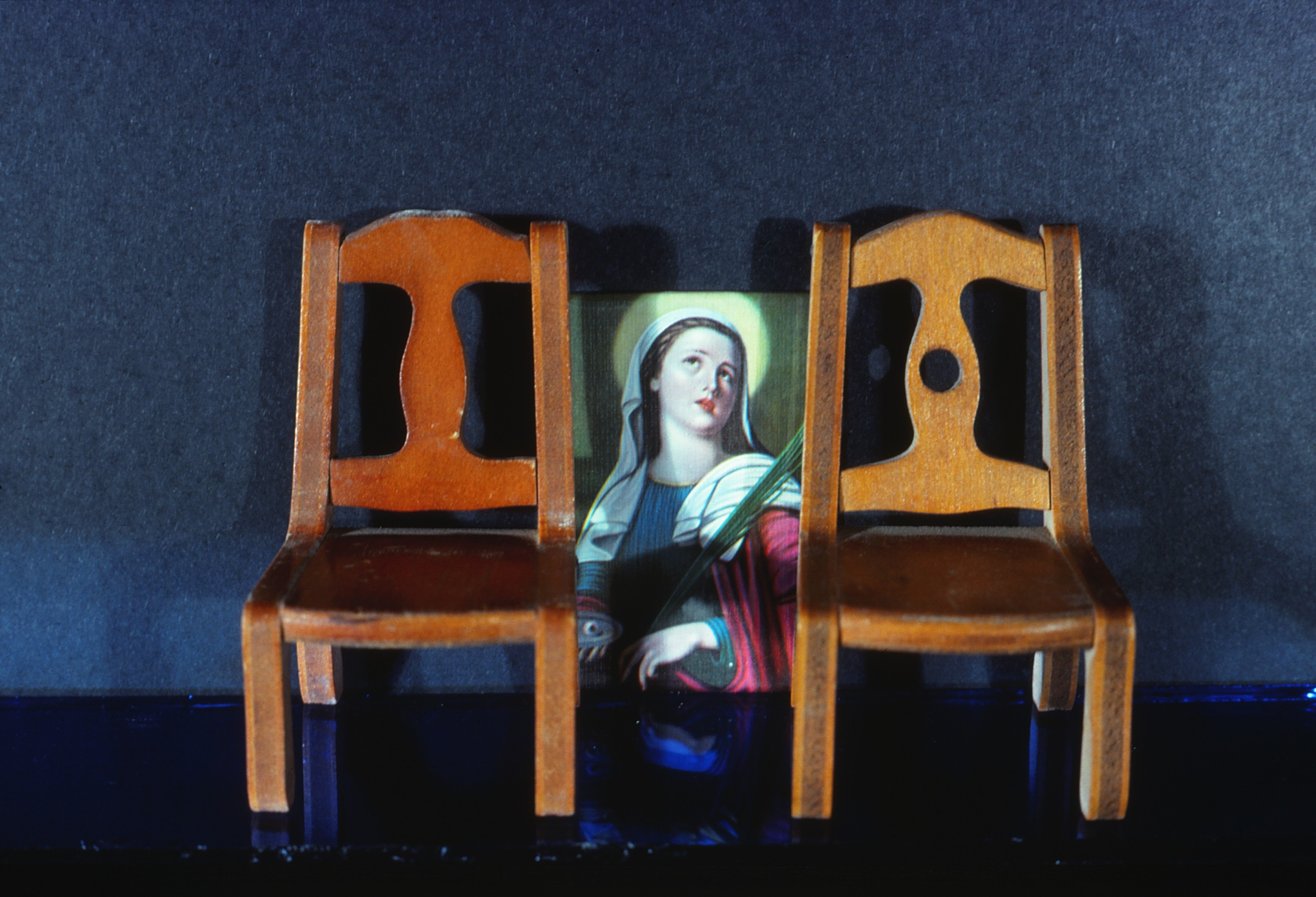 photo of two chairs with painting of the Madonna resting on the floor in between