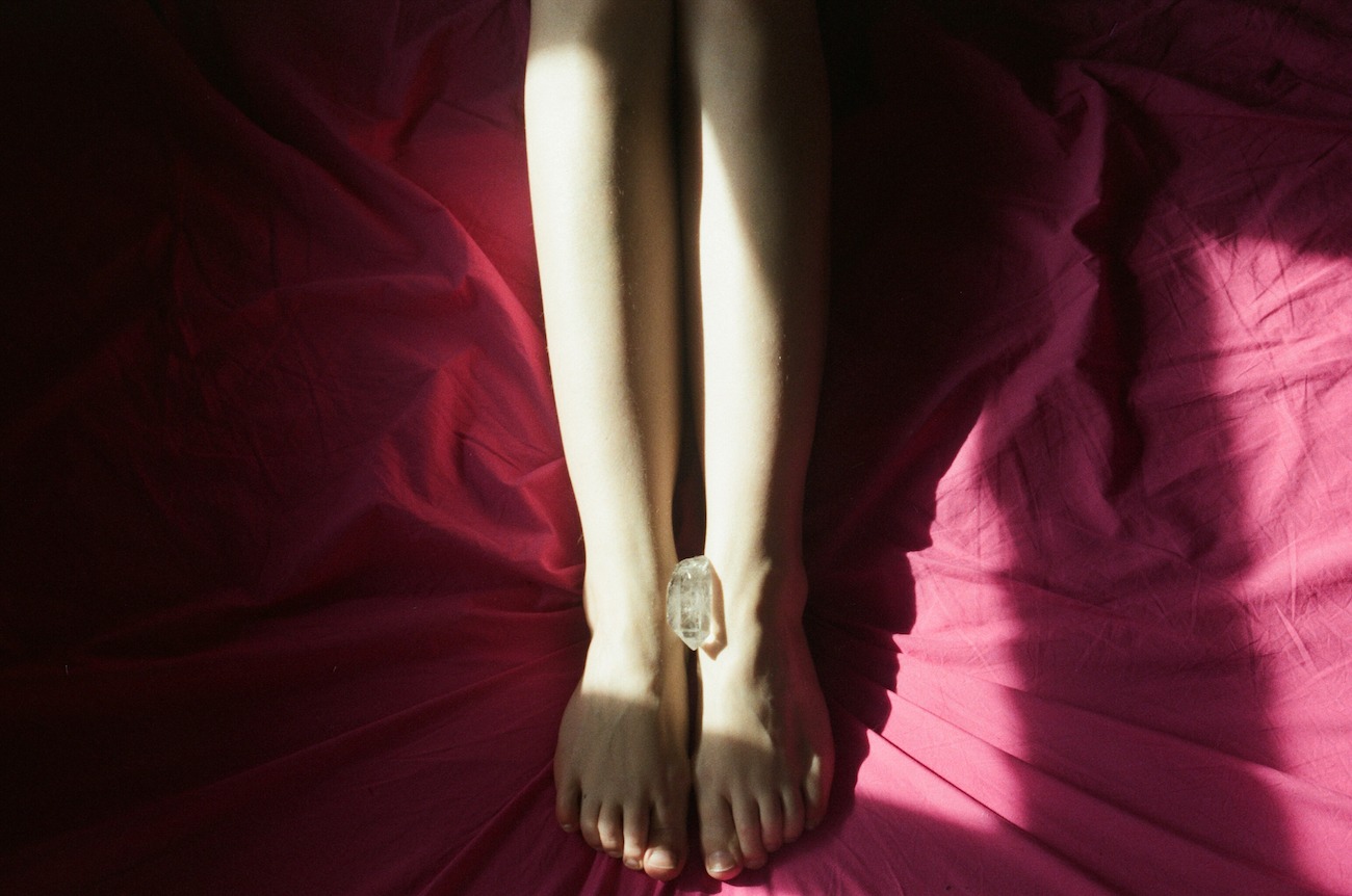 a photoof a piece of crystal is placed between a woman's feet who is in bed on red bedsheets from Lina Scheynius photo-essay for Tabayer jewelry Tabayer jewellery