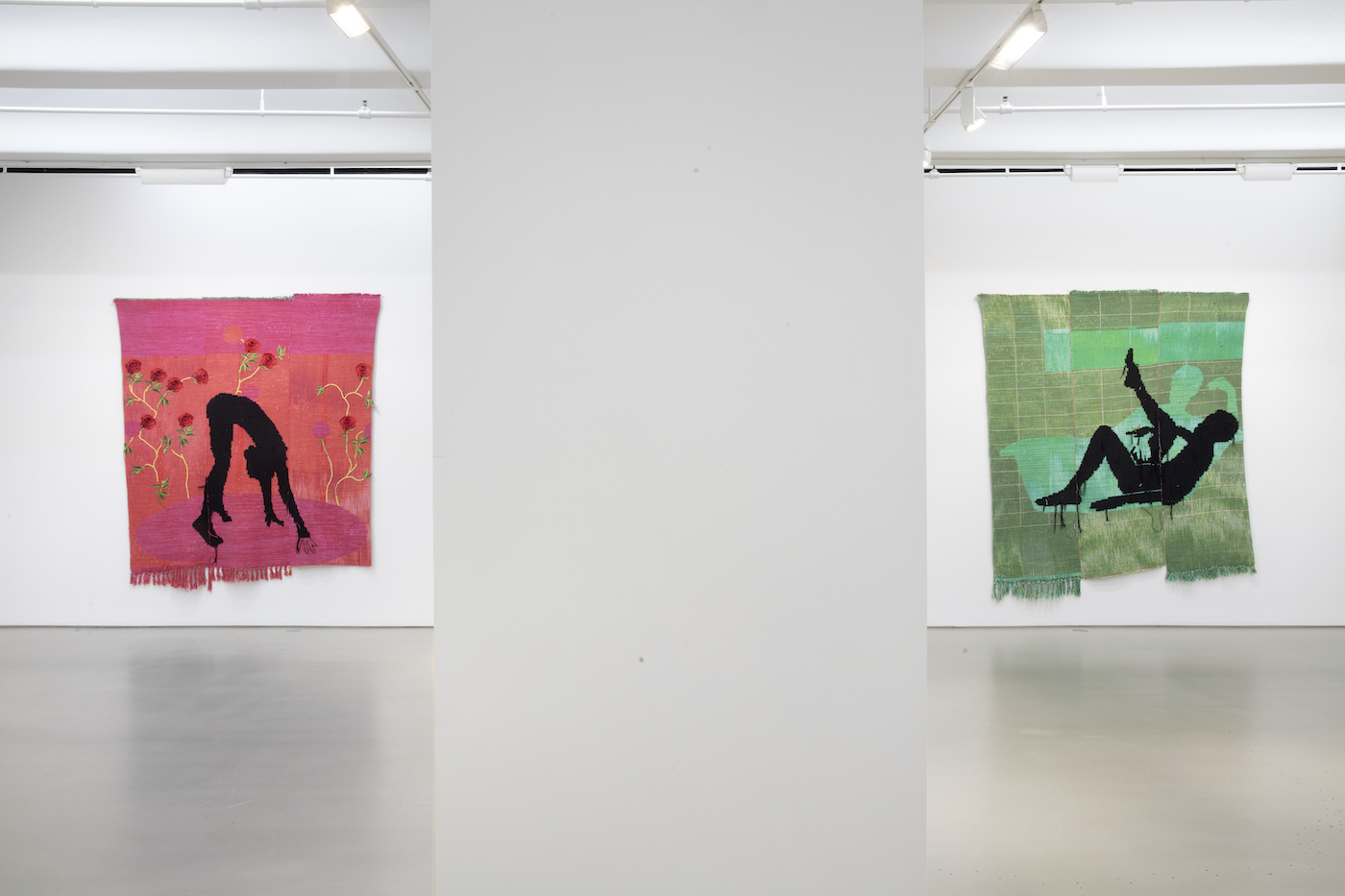 two textile print quilts by diedrick brackens in gallery space; two pieces depict silhouette figures against green and pink backgrounds