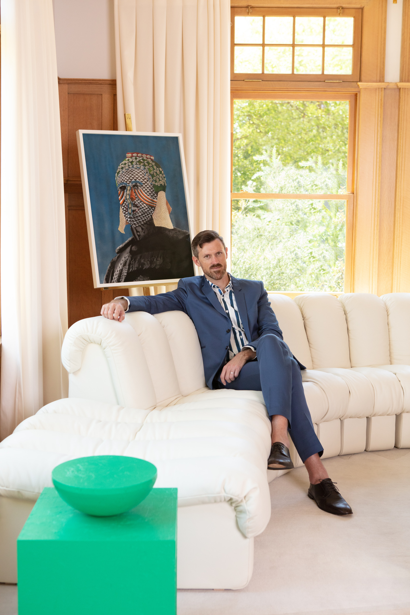 chet callahan in his home on white couch with blue portrait painting and window behind him