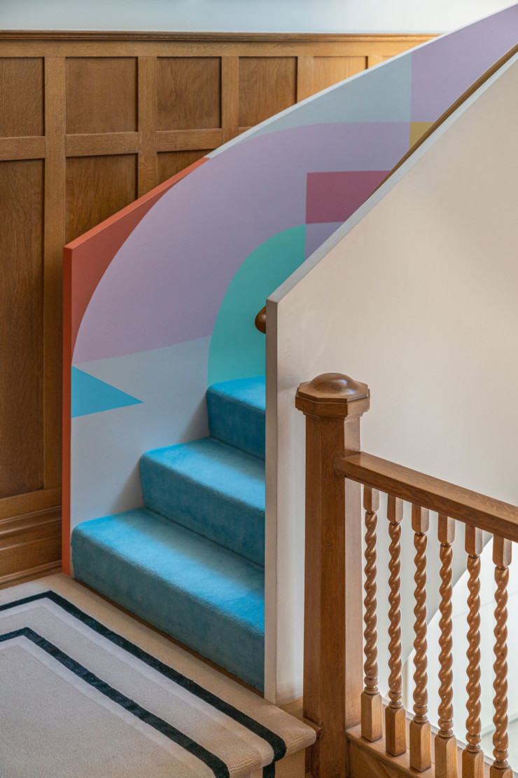 A custom mural by Adrian Kay Wong in a stairwell. All rugs by Ghislaine Vina for The Rug Company.