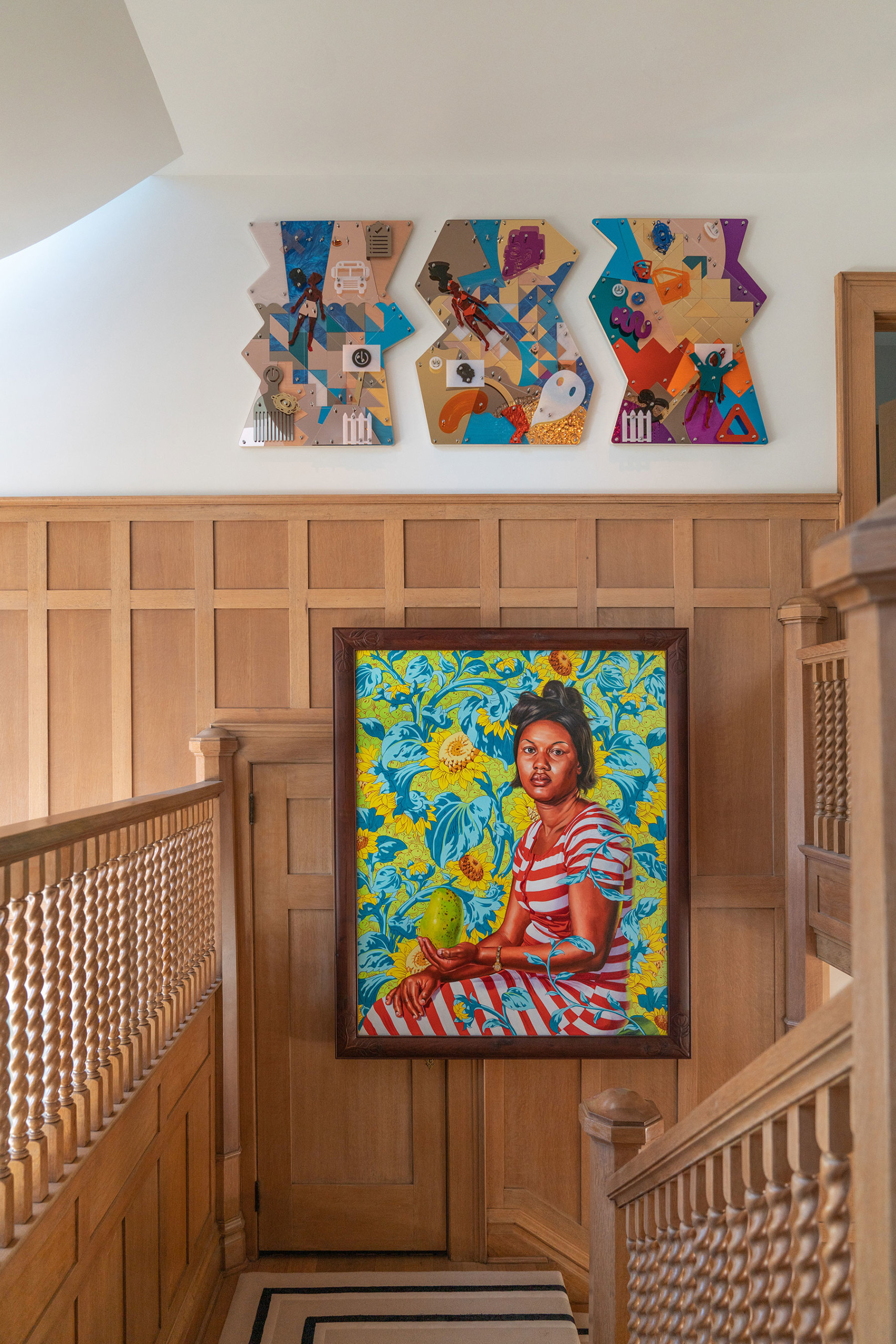 wooden stairwell space in chet callahan home featuring painting by kehinde wiley of portrait with 3 works by damien davis above