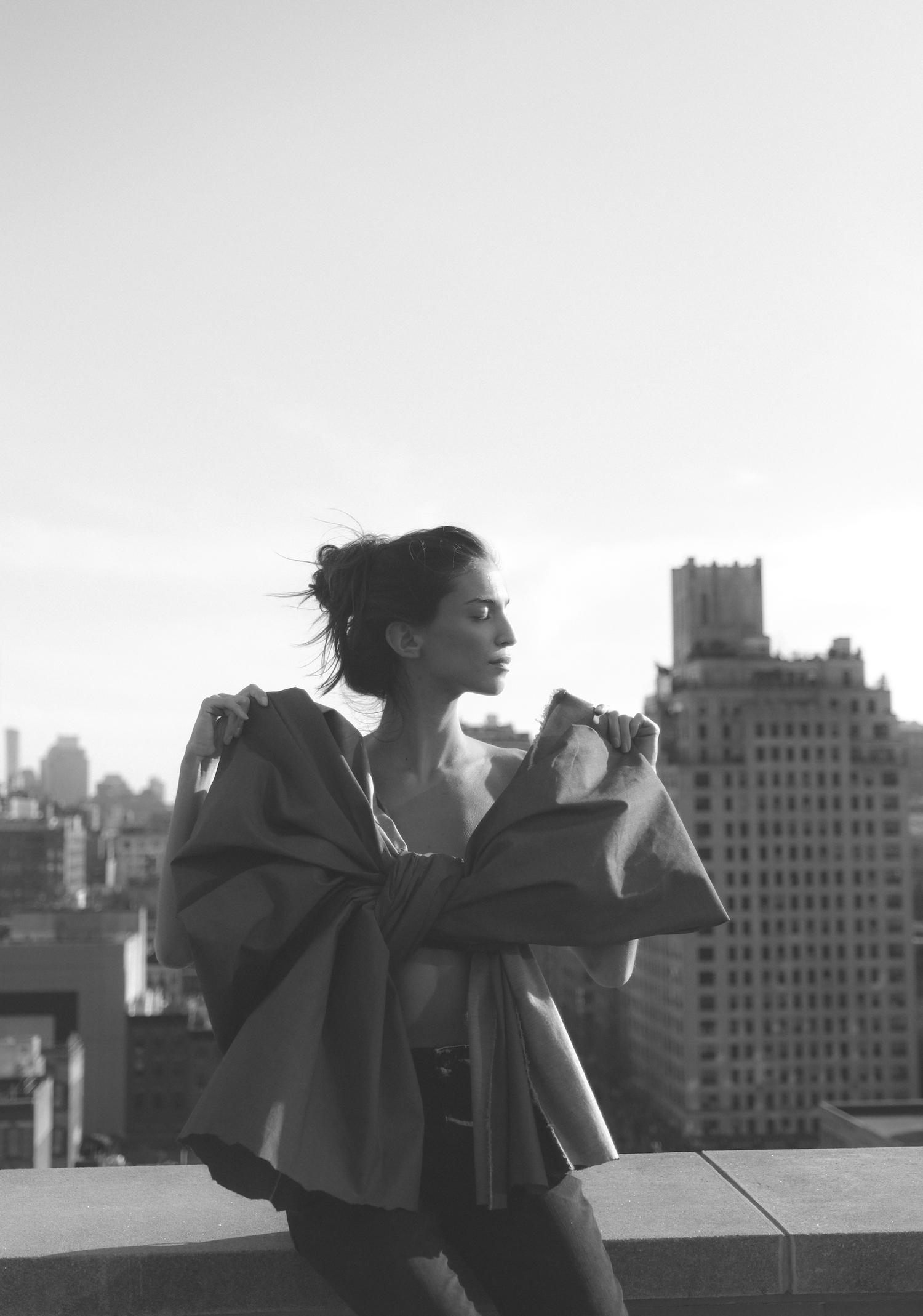 Marina Testino wrapped in a large isko denim bow on the roof with NYC in the background