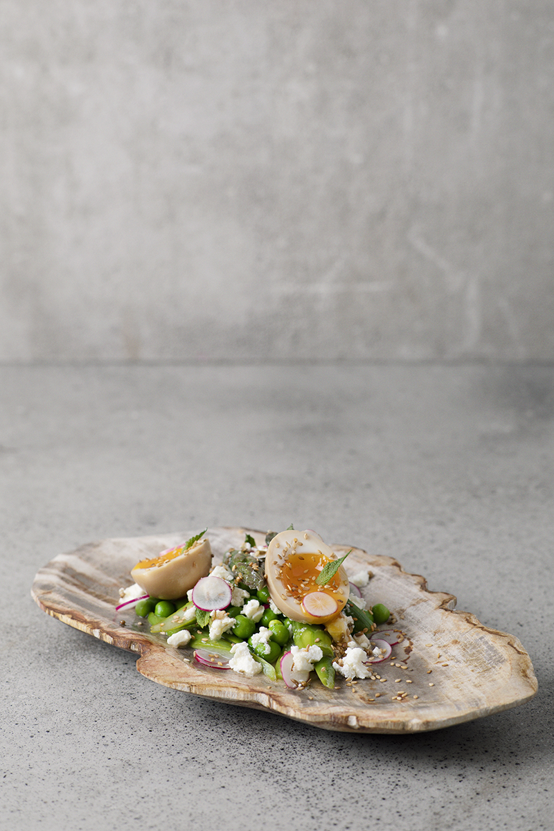 modern gourmet meal with eggs and edamame and radish on oyster-like wooden plate at paris restaurant FOREST