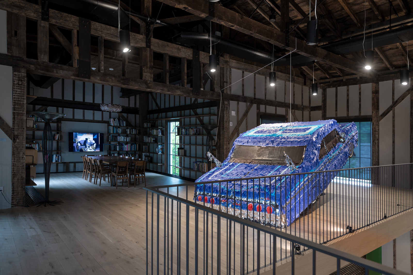 installation view of road rage at the church, showing sparkling blue car made of confetti pieces hanging