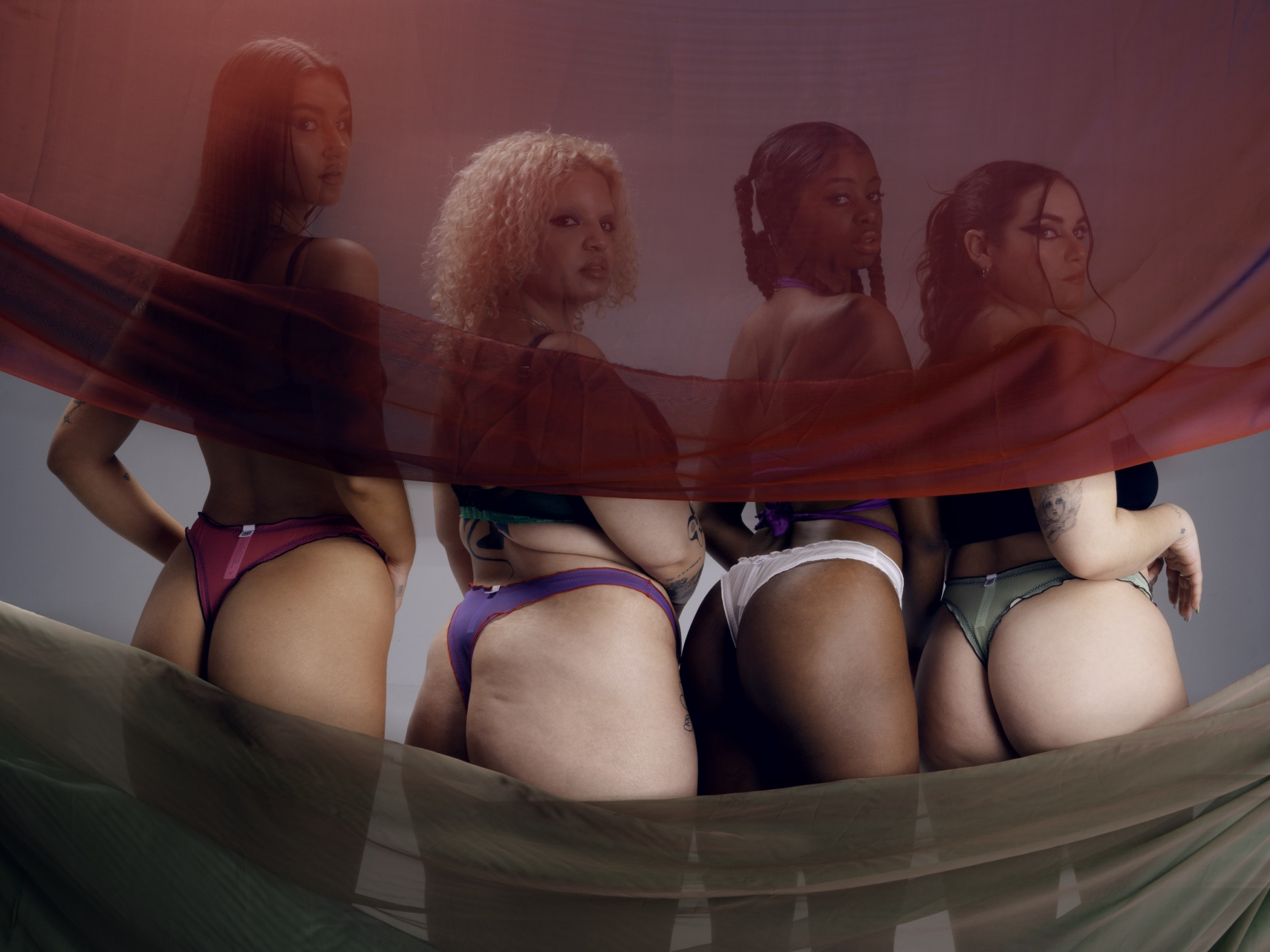 4 models wearing siren basics mesh thongs have back to the camera, with red mesh fabric covering their heads, with heads turned and looking at camera