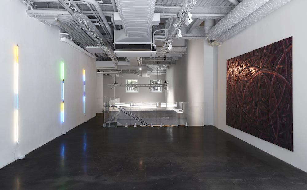 installation view of shady beautiful at malin gallery with three LED poles on one wall and on the other an abstract painting with swirls