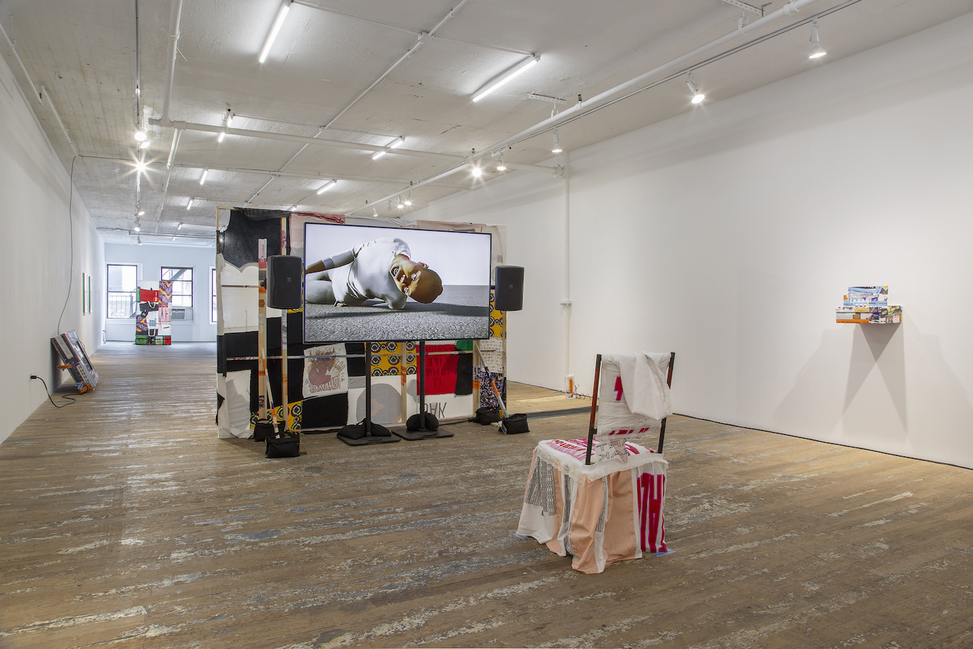 installation view of martine syms loot sweets, with makeshift tv theater made of textiles and objects in gallery space