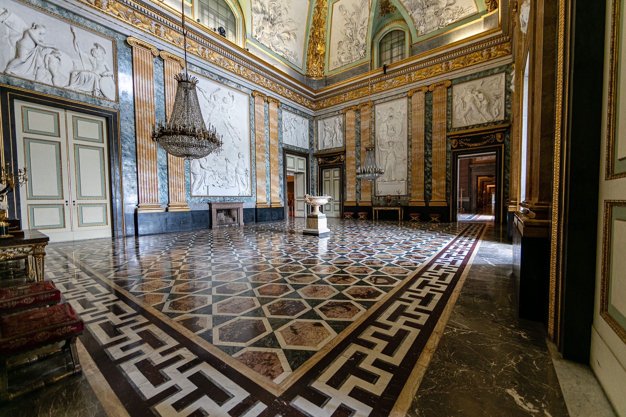 large room in royal palace of caserta with chandelier