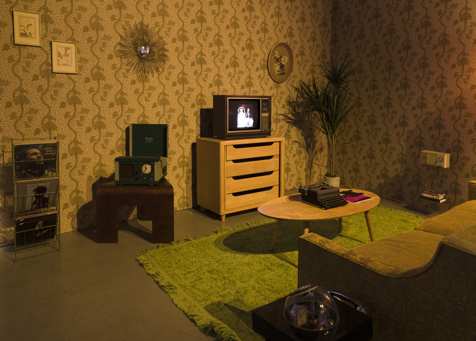installation view of blitz bazawule's a moment in time at uta artist space, with dark, yellow-toned room with retro TV, couch, wallpaper and magazine rack
