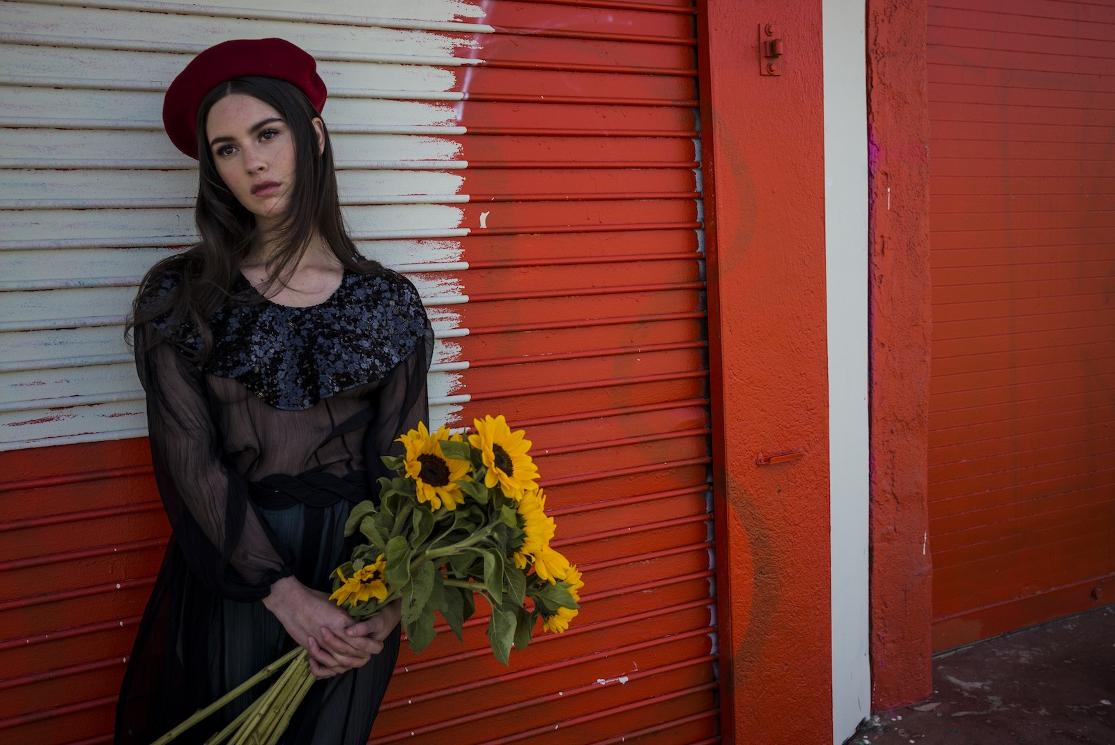 artists on tour gracie abrams against red wall wearing red beret and holding bouquet of sunflowers