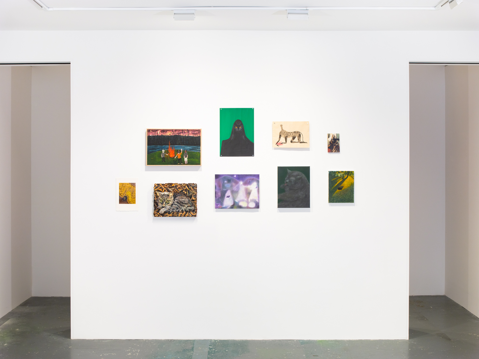 installation view of nine lives show at fortnight institute in nyc - white wall with various paintings of animals