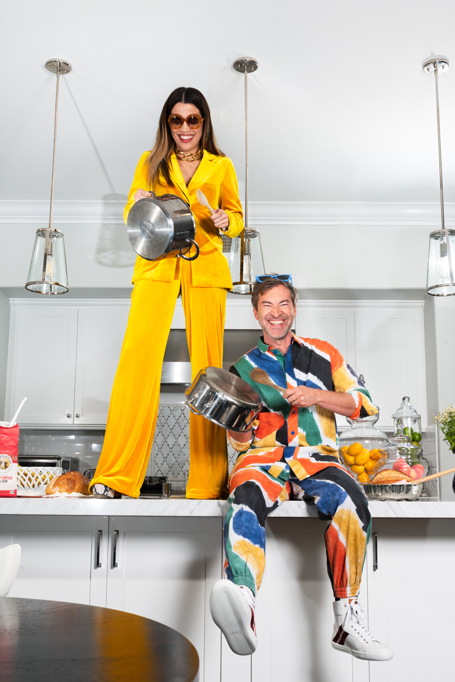 Mark Duplass sits and Natalie Morales stands on a kitchen countertop holding pots and laughing.