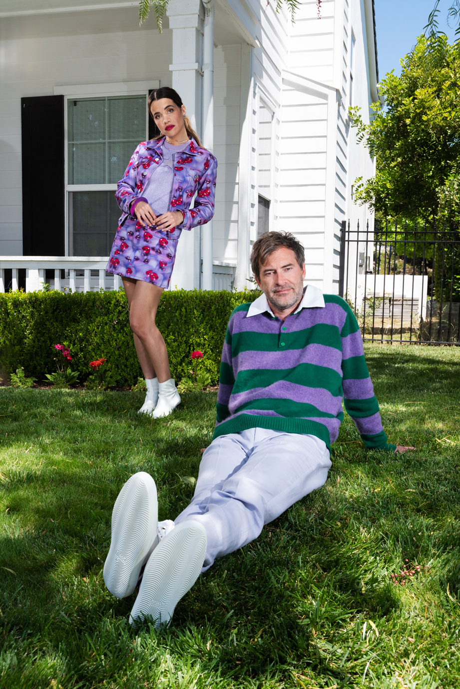 Mark Duplass and Natalie Morales pose on the yard outside of a home.